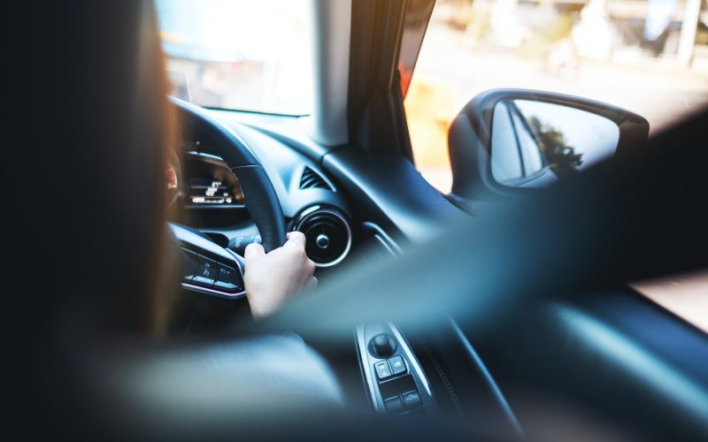 a woman holding steering wheel with seat belt fastened while driving a car on the road
