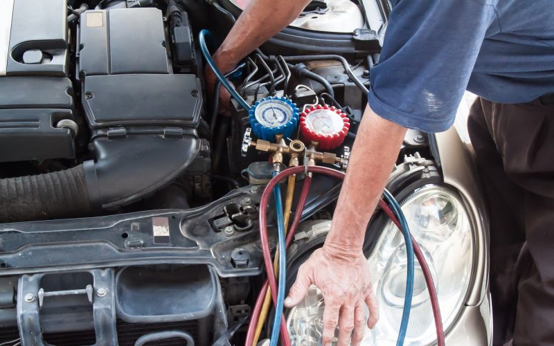 Mechanic with manometer inspecting auto vehicle air-condition co