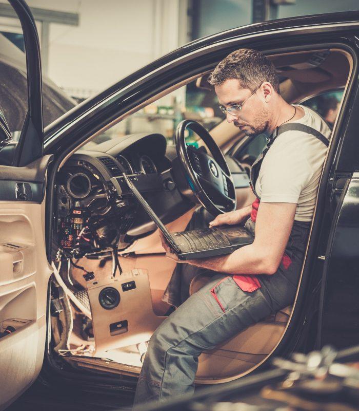 Serviceman making car diagnostics with laptop in a workshop