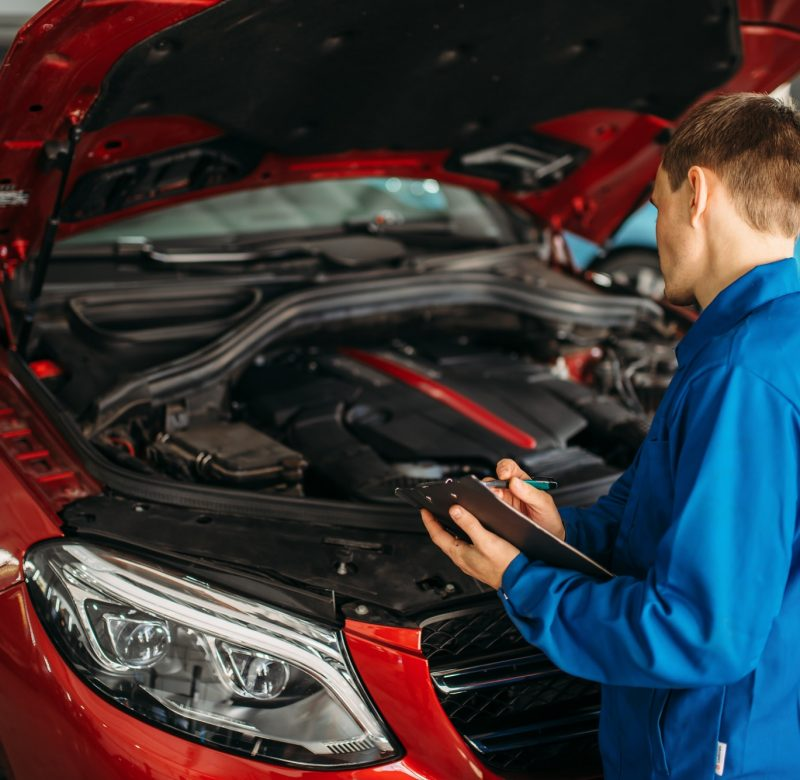 Technician with notebook, car with opened hood