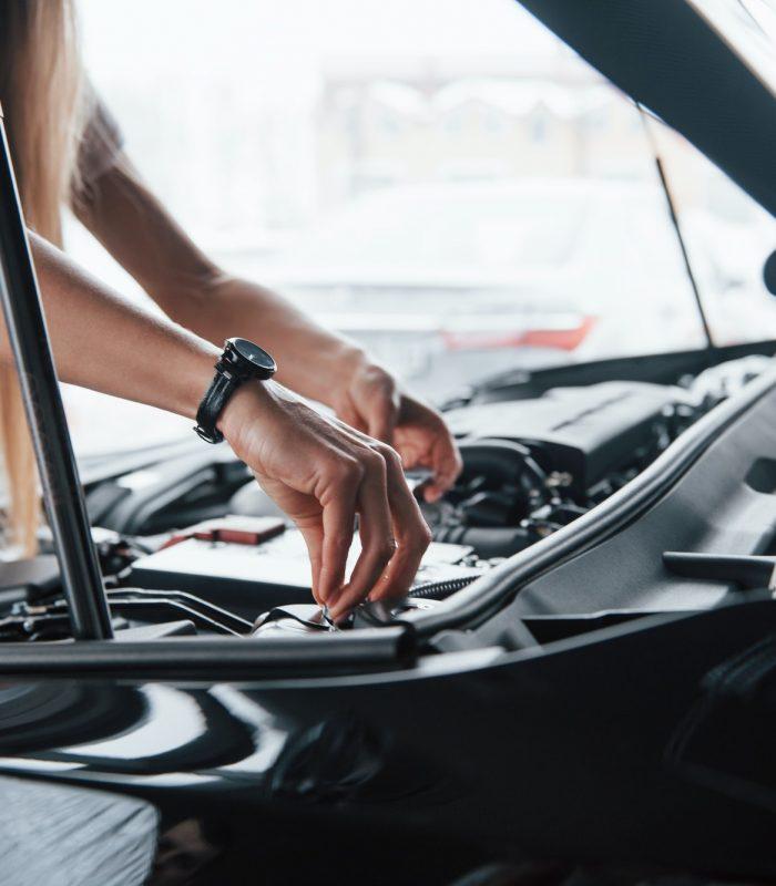 Tuning the details. On the lovely job. Car addicted woman repairs black automobile indoors