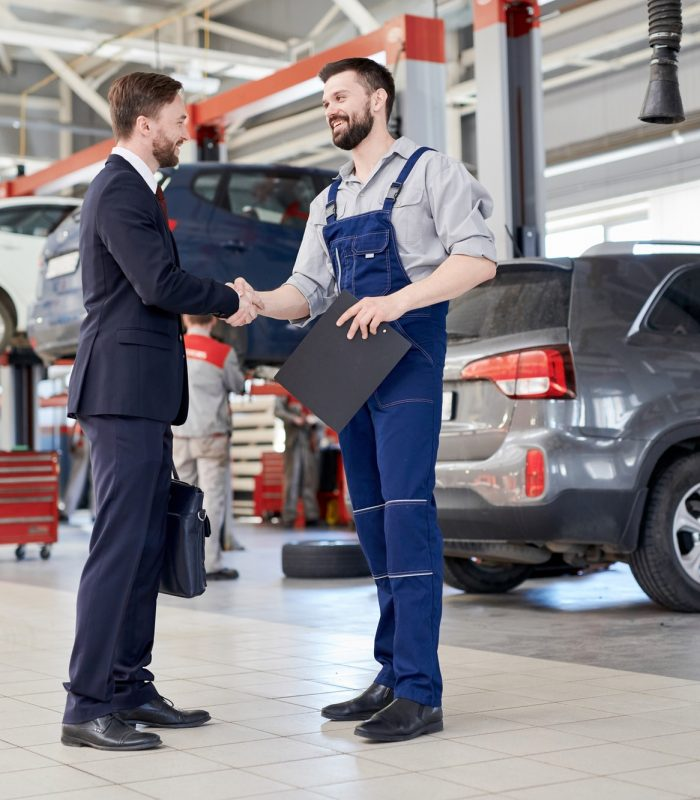 Worker Shaking Hands with Client in Car Service Shop